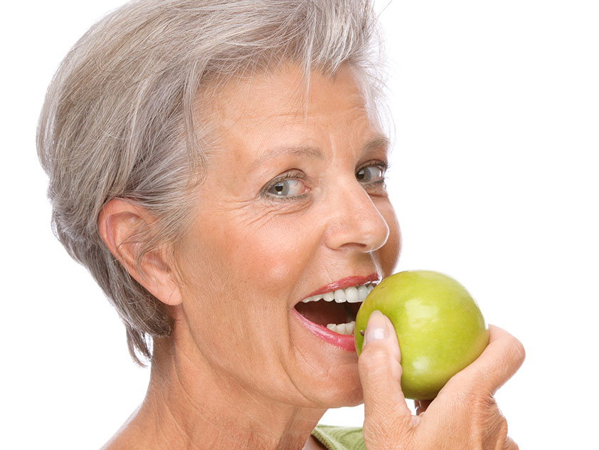 Lady biting in apple with dentures