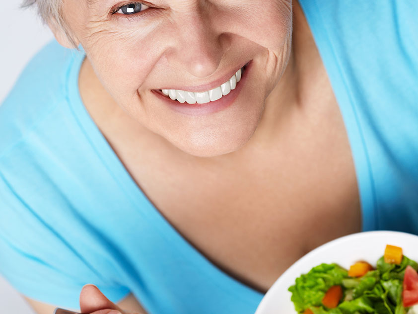 Lady eating meal with dentures
