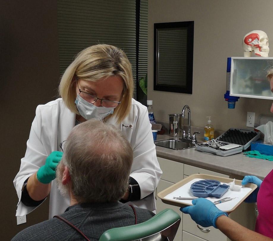 Nancy Tomkins working on dental implants